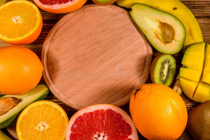 Todav?a vida con las frutas y la tabla de cortar ex?ticas Pl?tanos, mango, naranjas, aguacate, pomelo y kiwis en la tabla de made fotos de archivo
