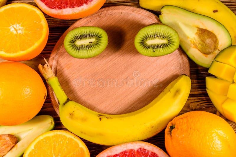 Todav?a vida con las frutas y la tabla de cortar ex?ticas Pl?tanos, mango, naranjas, aguacate, pomelo y kiwis en la tabla de made fotografía de archivo