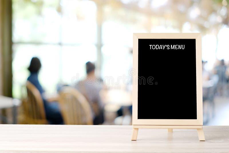 Today's menysvart tavla, teckenbräde, på tabellen på suddighetscoffee shop, restaurang, med folkbakgrund, svart tavlaåtlöje för royaltyfri bild