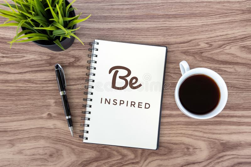 Today Inspirational quote- Be inspired. With positive motivational text on a notebook, a cup of morning black coffee, a pen and stock photography