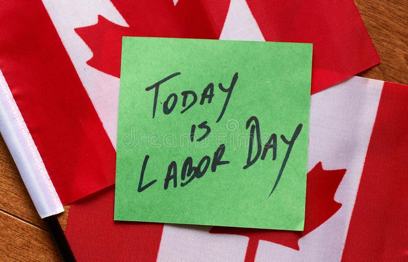 Today is Labor Day. Written on a green sticky note, the note is lying on Canadian flags stock photo