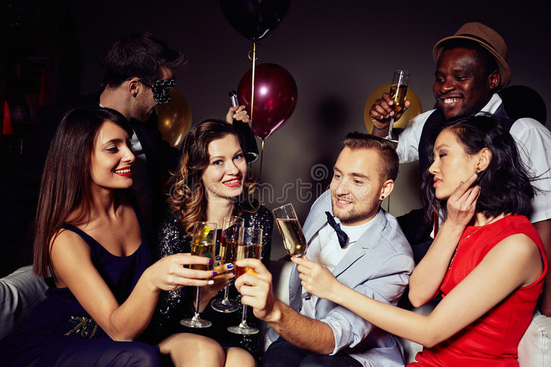 Today is My Birthday!. Multi-ethnic group of young people gathered together at home party in order to celebrate birthday of their friend, they toasting with royalty free stock photo