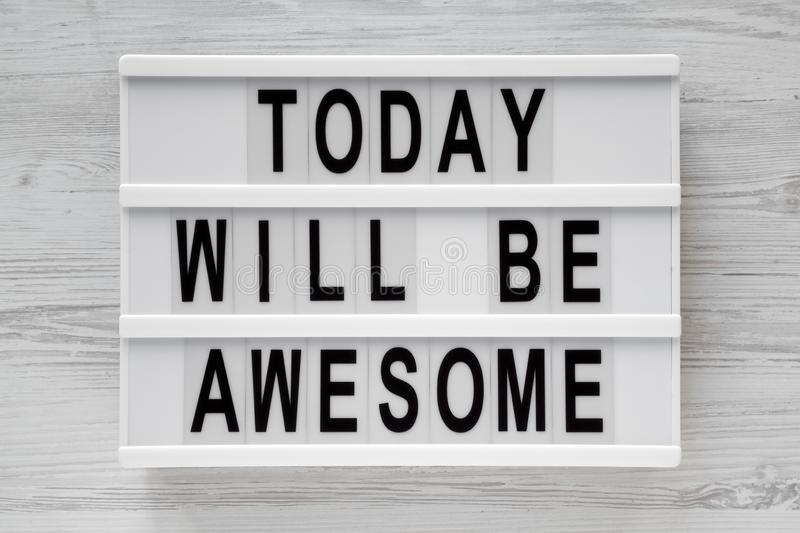 `Today will be awesome` words on lightbox over white wooden surface, top view. stock image