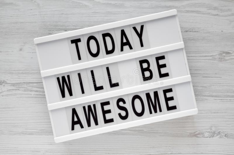 `Today will be awesome` words on modern board over white wooden surface, overhead view. royalty free stock image