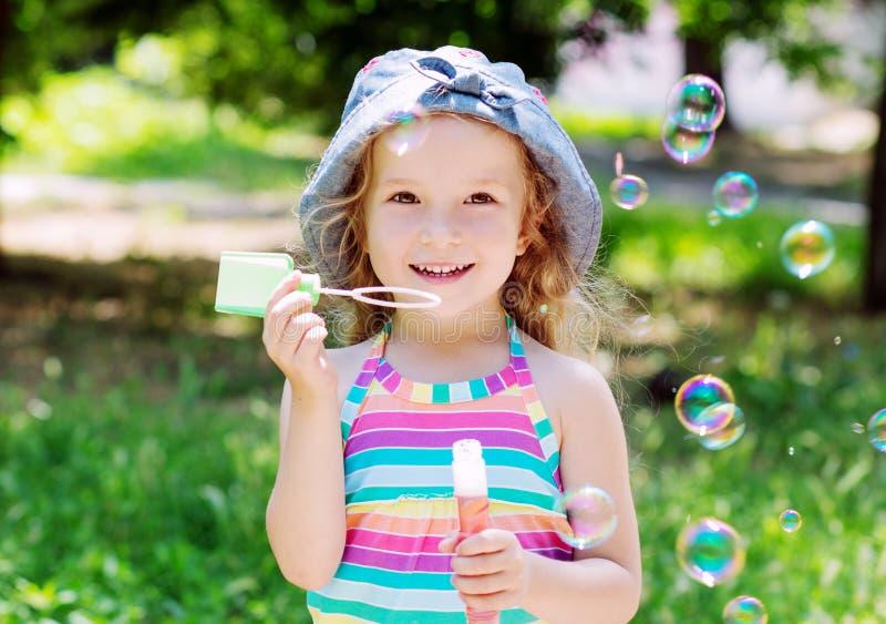 Todddler lycklig flicka som blåser såpbubblor royaltyfri bild