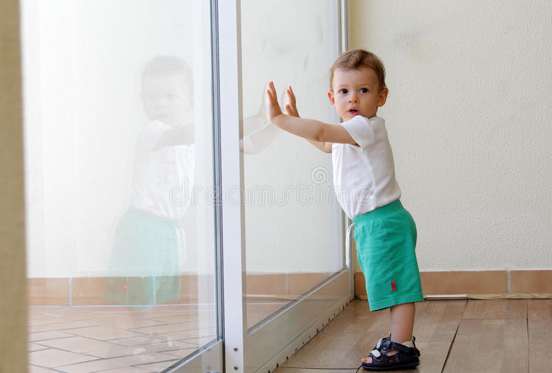Toddler against glass door. Toddler leaning against a glass sliding door in daylight royalty free stock photo