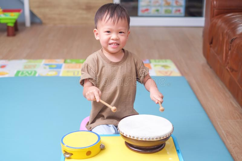 Toddler baby boy child hold sticks & plays a musical instrument drum stock photography