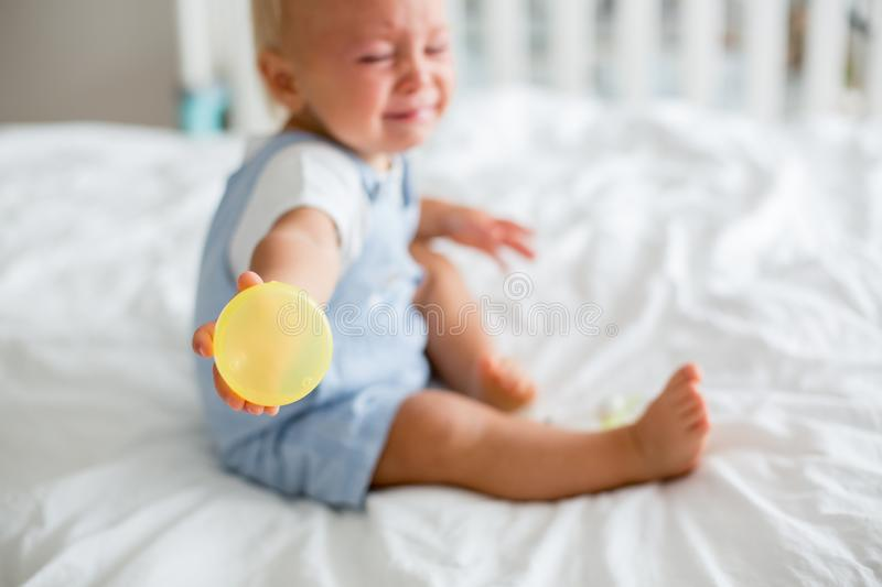Toddler baby boy, playing with dummy, crying unhappy for the pac royalty free stock photo
