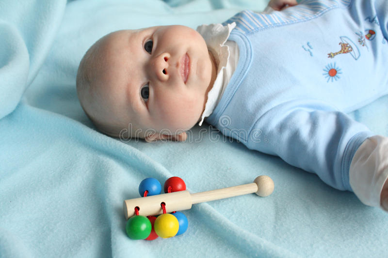Toddler baby boy with a rattle royalty free stock photos