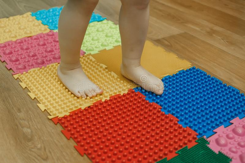 Toddler on baby foot massage mat. Exercises for legs on orthopedic massage carpet. Orthopedic massage puzzle floor mats royalty free stock photos
