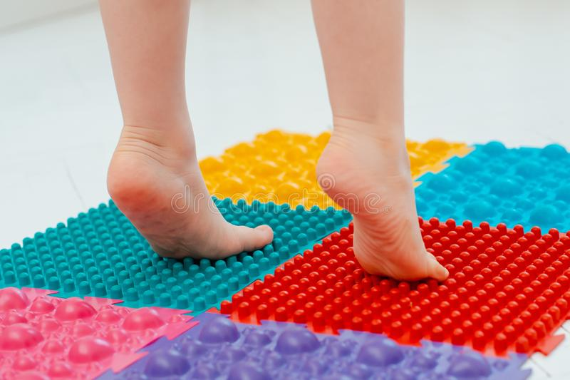 Toddler on baby foot massage mat. Exercises for legs on orthopedic massage carpet. prevention of flat feet and hallux valgus stock images