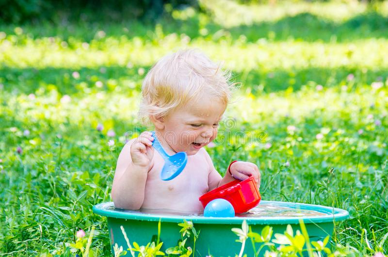 Toddler baby girl with blue eyes having fun with water stock image
