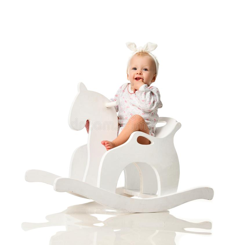 Toddler baby girl is riding swinging on a rocking chair toy horse over white royalty free stock photography