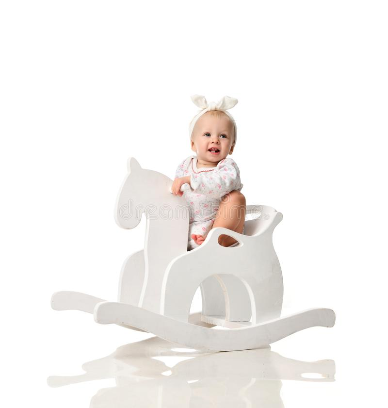 Toddler baby girl is riding swinging on a rocking chair toy horse over white stock photography
