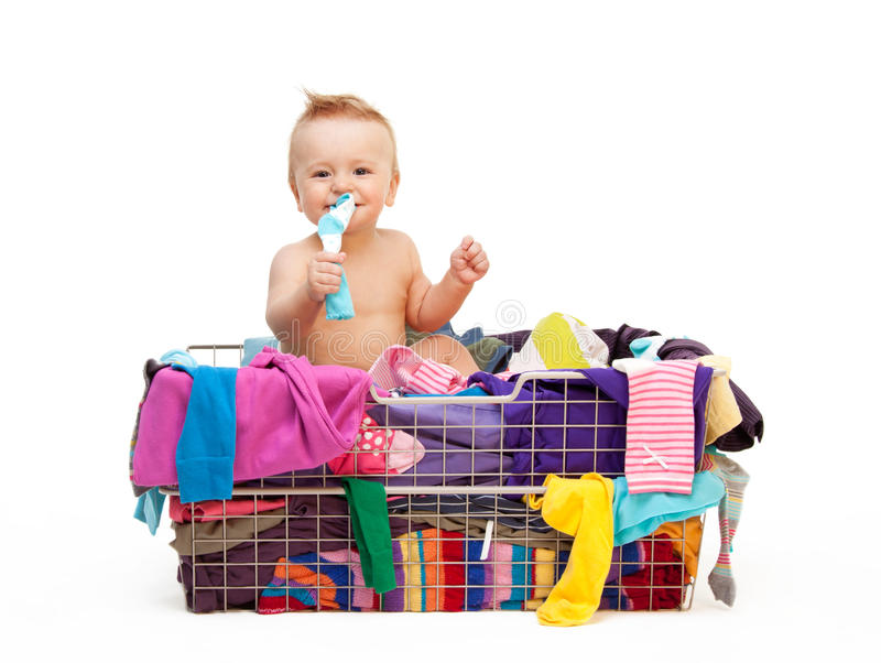 Toddler in basket with clothes stock image