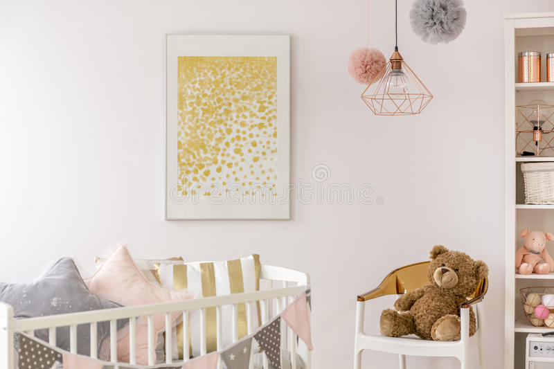 Toddler bedroom with white crib. Poster, chair and teddy bear stock photography