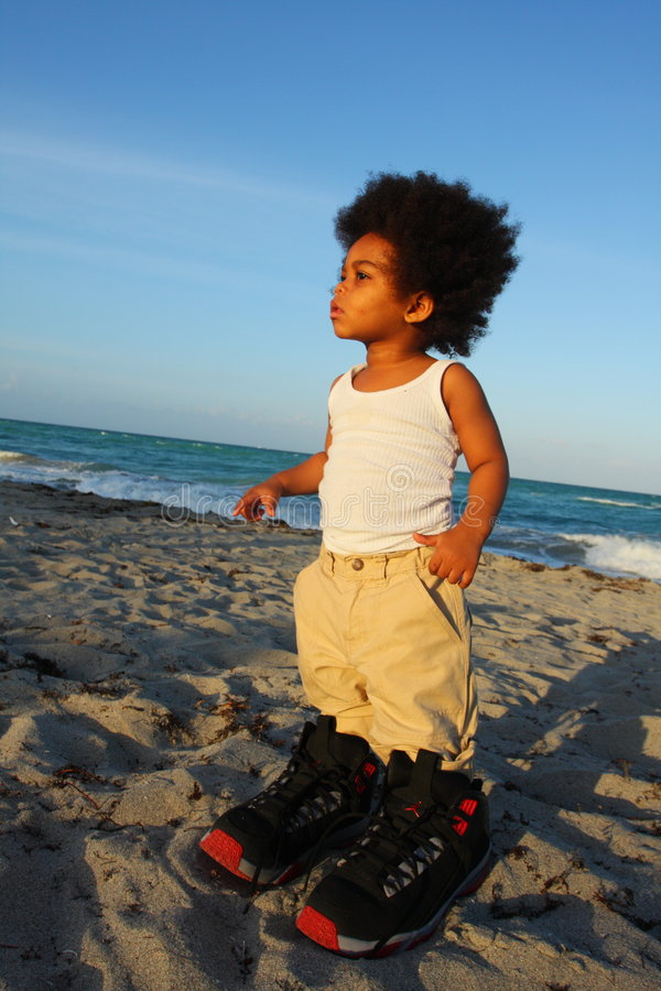 Toddler in Big Shoes. Little toddler wearing really big shoes royalty free stock images