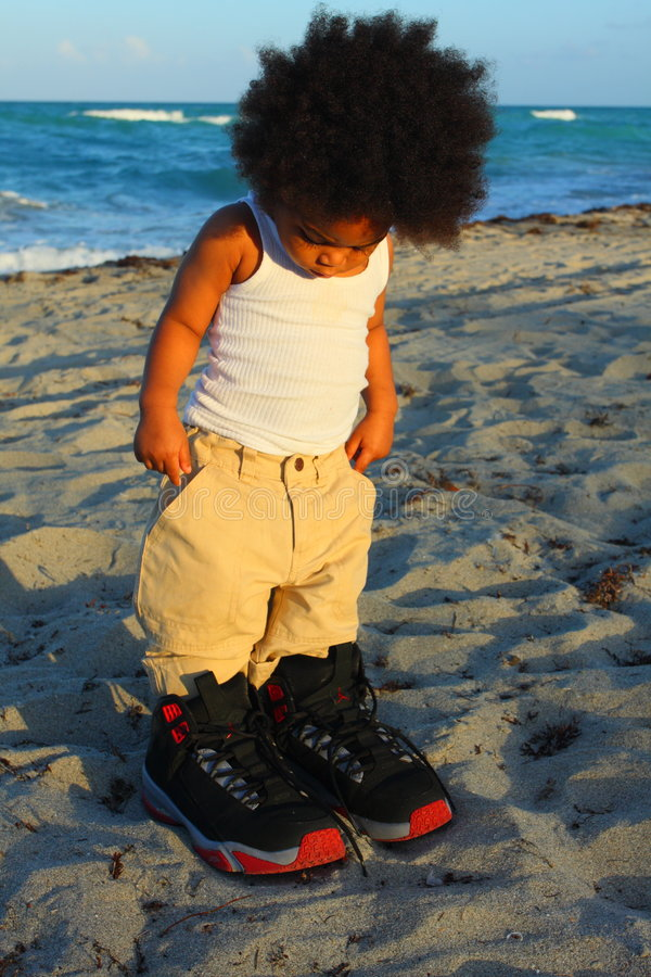 Toddler in Big Shoes. Little toddler wearing really big shoes stock photography