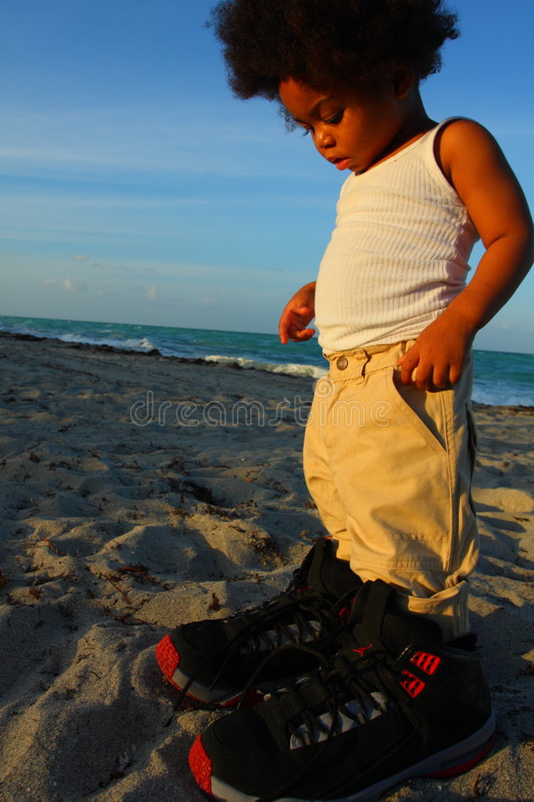 Toddler in Big Shoes. Little toddler wearing really big shoes stock photos