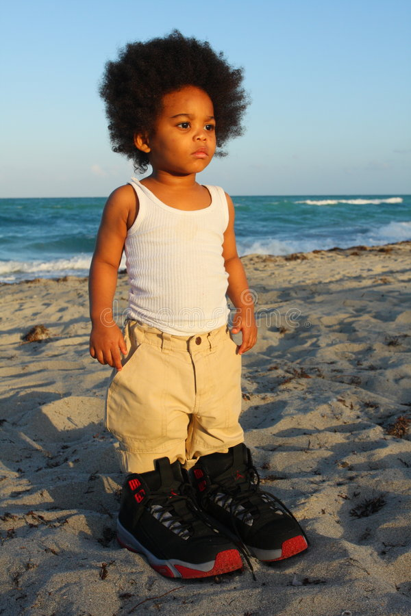 Toddler in Big Shoes. Little toddler wearing really big shoes. Ocean in the background royalty free stock photos