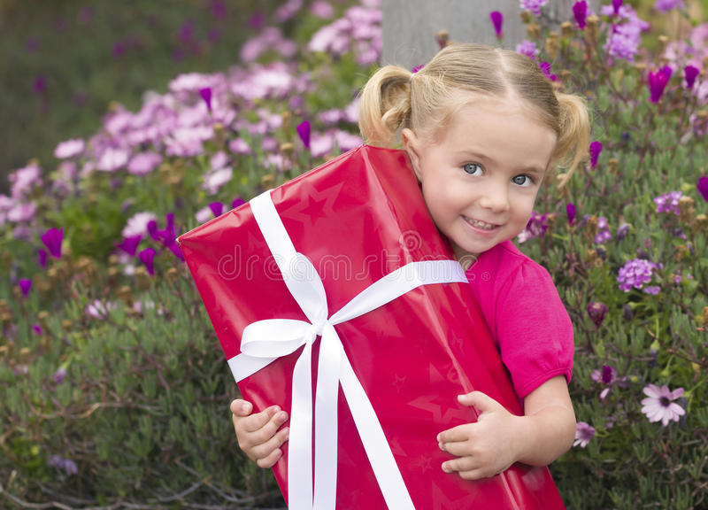 Little Girl With Birthday Present. A toddler with blond hair in pig tails and blue eyes holds a very large birthday present wrapped in a red box and tied with a stock image