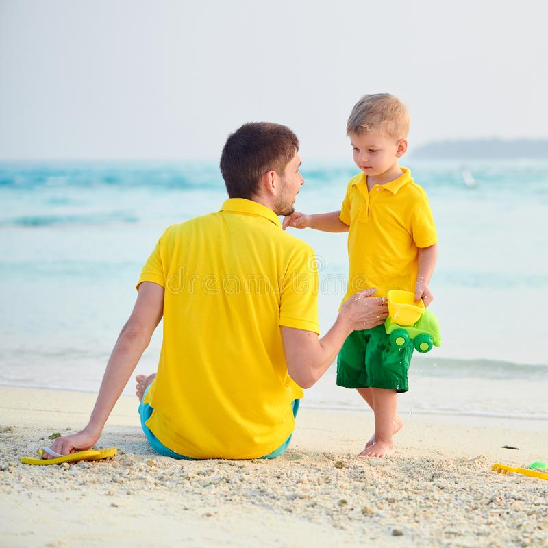 Toddler boy on beach with father stock photos
