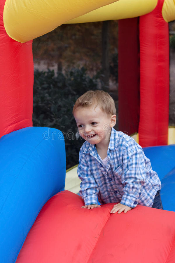 Toddler Boy in Bounce House. Happy young toddler boy on moonbounce inflatable party bounce house royalty free stock images
