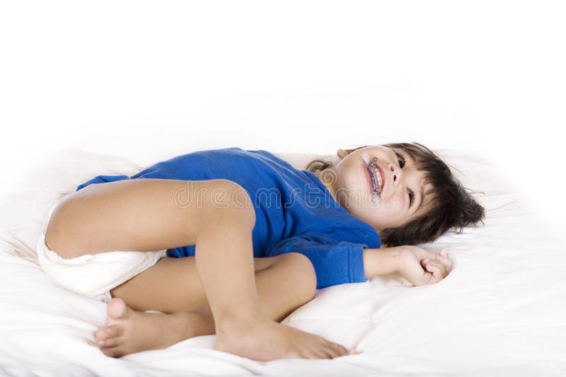 Toddler boy with cerebral palsy. Happy disabled toddler boy with cerebral palsy lying down stock photography