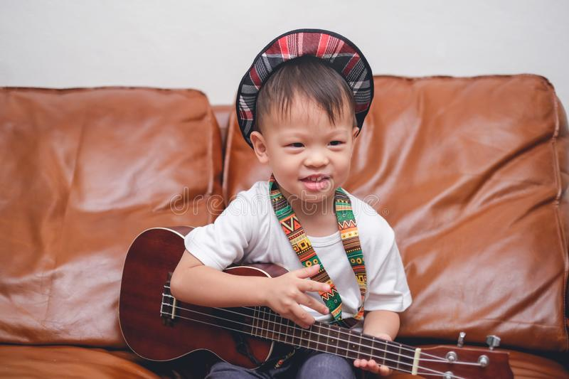Toddler boy child wearing hat hold & play Hawaiian guitar or ukulele in living room at home royalty free stock photo