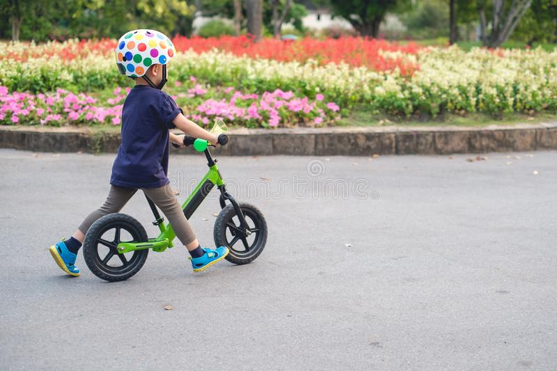 Toddler boy child wearing safety helmet learning to ride first balance bike royalty free stock photos