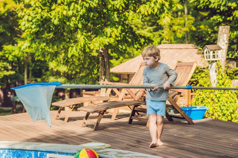 The Toddler boy cleans the pool and pulls the ball out of the po royalty free stock photography