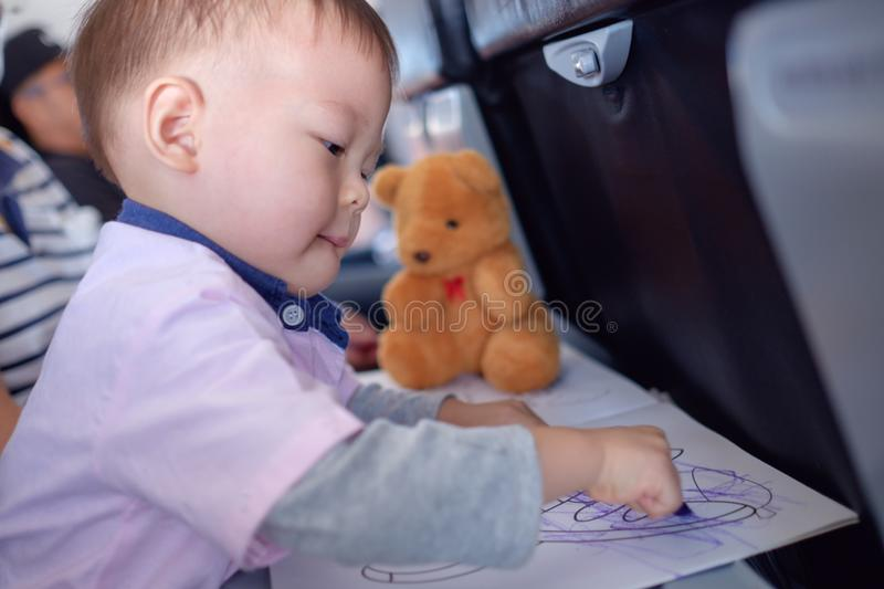 Toddler boy coloring in coloring book with crayons during flight on airplane. Little Asian 1 year old toddler boy coloring in coloring book with crayons during stock photos
