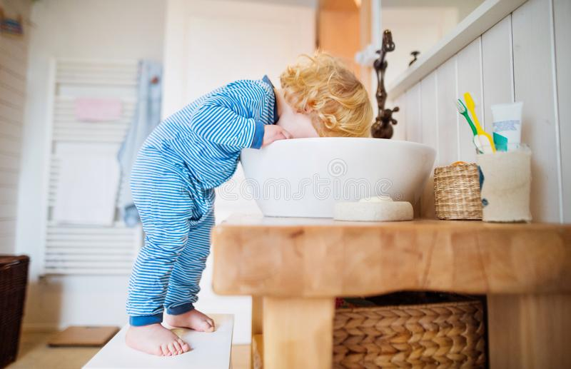 Toddler boy in a dangerous situation in the bathroom. royalty free stock photos