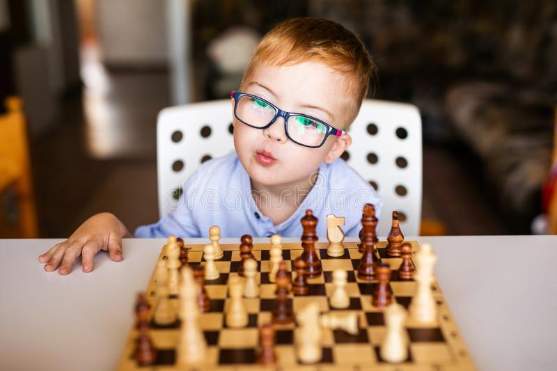 Toddler boy with down syndrome with big blue glasses playing chess in kindergarten.  royalty free stock photography