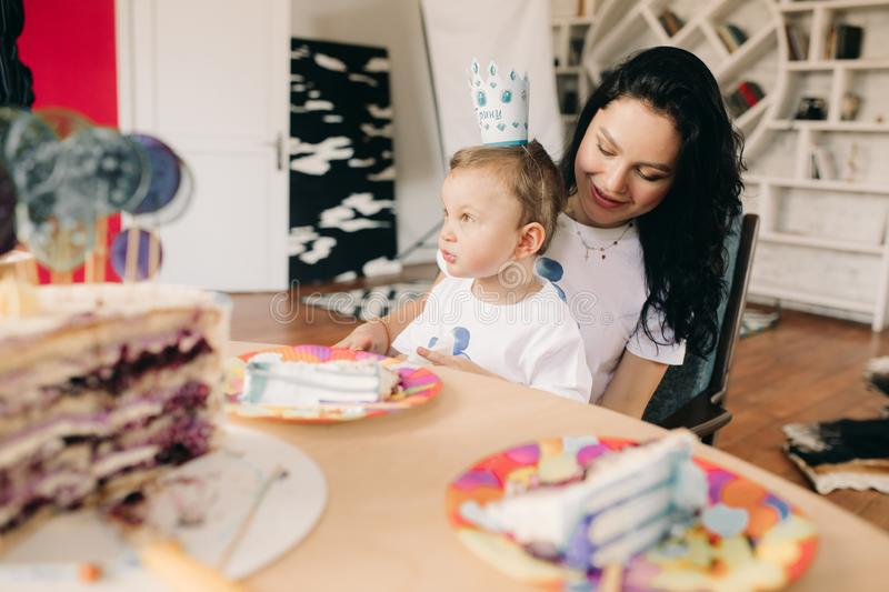 Toddler boy eaches cake for birthday next to his mother. Toddler boy eaches cake for birthday on the table next to his mother royalty free stock photography