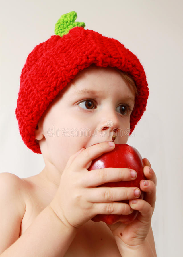 Toddler boy eating an apple stock images