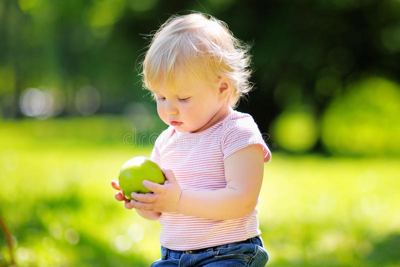 Toddler boy eating fresh green apple royalty free stock images