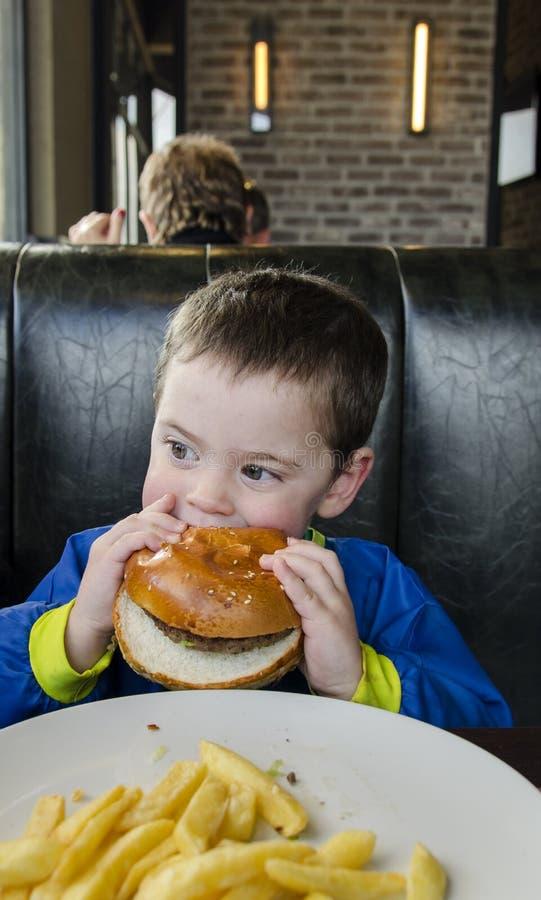 Toddler boy eating Hamburger and fries royalty free stock photos