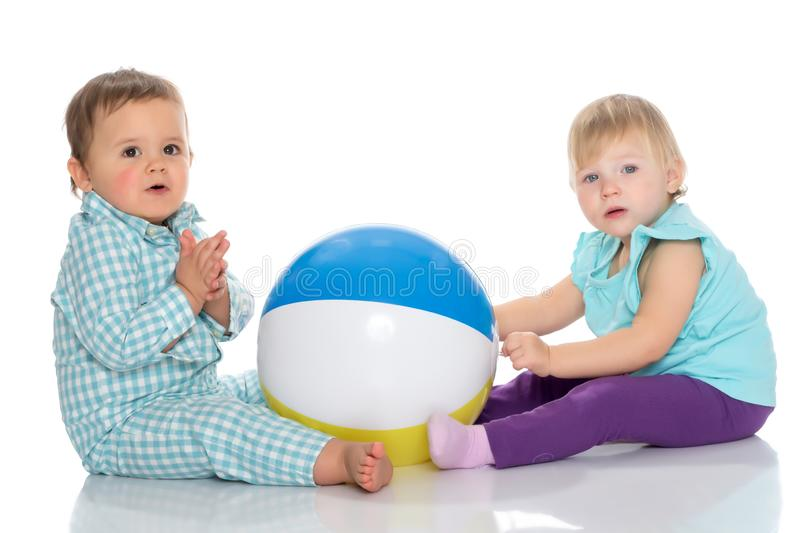 Toddler boy and girl playing with ball. stock photos