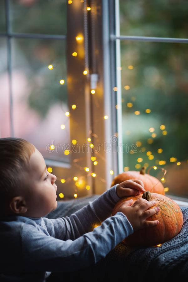 Toddler boy holding orange pumpkin on gray knitted plaid near window in evening surrounded with warm garland lights with golden. Bokeh. October autumn harvest royalty free stock photography