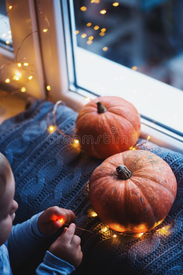 Toddler boy holding orange pumpkin on gray knitted plaid near window in evening surrounded with warm garland lights with golden. Bokeh. October autumn harvest stock photography