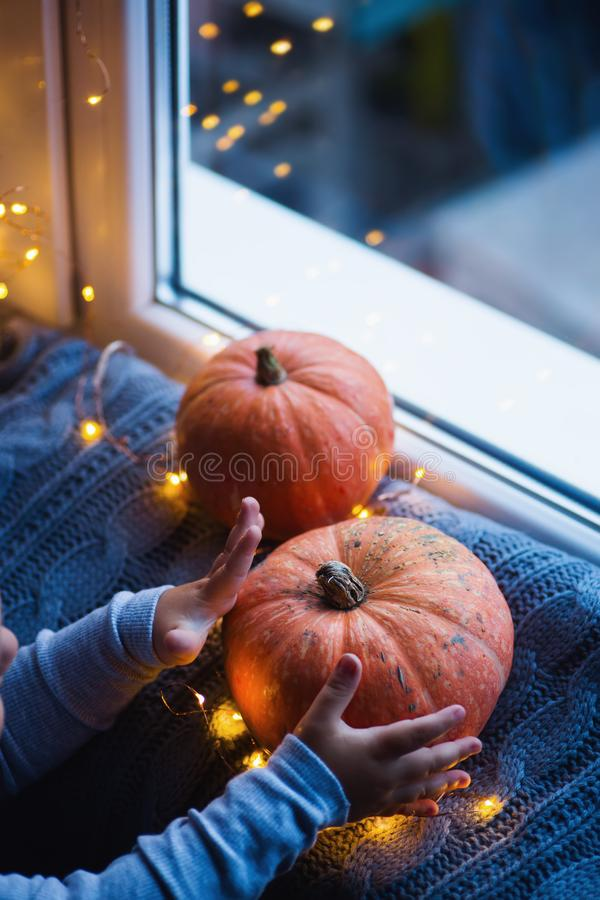 Toddler boy holding orange pumpkin on gray knitted plaid near window in evening surrounded with warm garland lights with golden. Bokeh. October autumn harvest stock photo