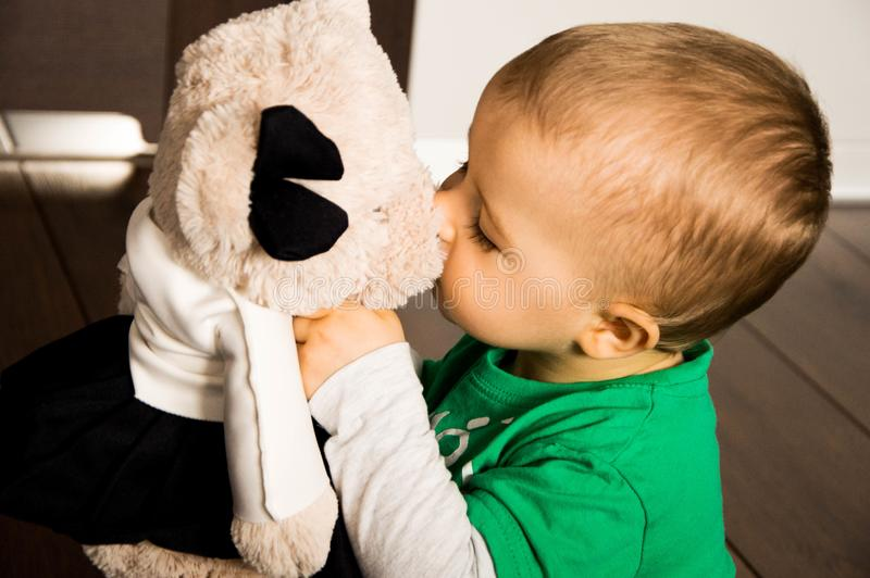 Toddler boy kissing teddy bear royalty free stock images