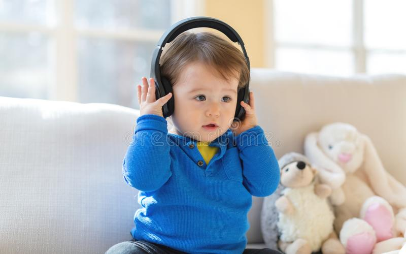 Toddler boy listening to music with headphones. Toddler boy listening to music with big headphones stock image