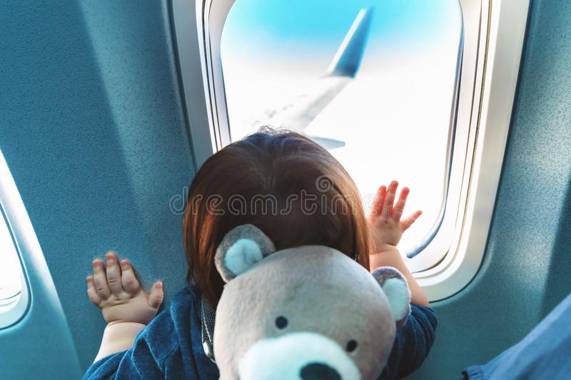 Toddler boy looking out a plane window. Little toddler boy looking out an airplane window while flying stock images