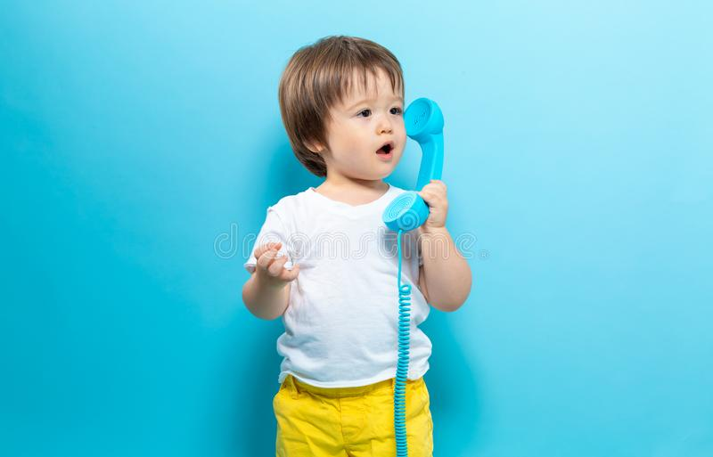 Toddler boy with an old fashioned phone. On a blue background royalty free stock image