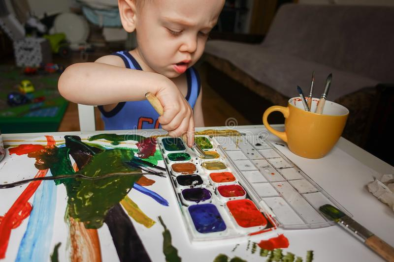 Toddler boy painting at home stock photography