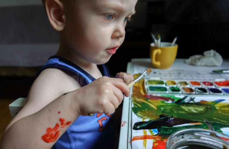 Toddler boy painting at home royalty free stock image