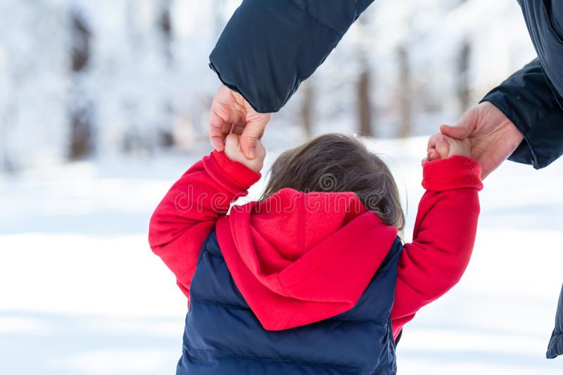 Toddler boy playing in the snow. With his mother royalty free stock photography