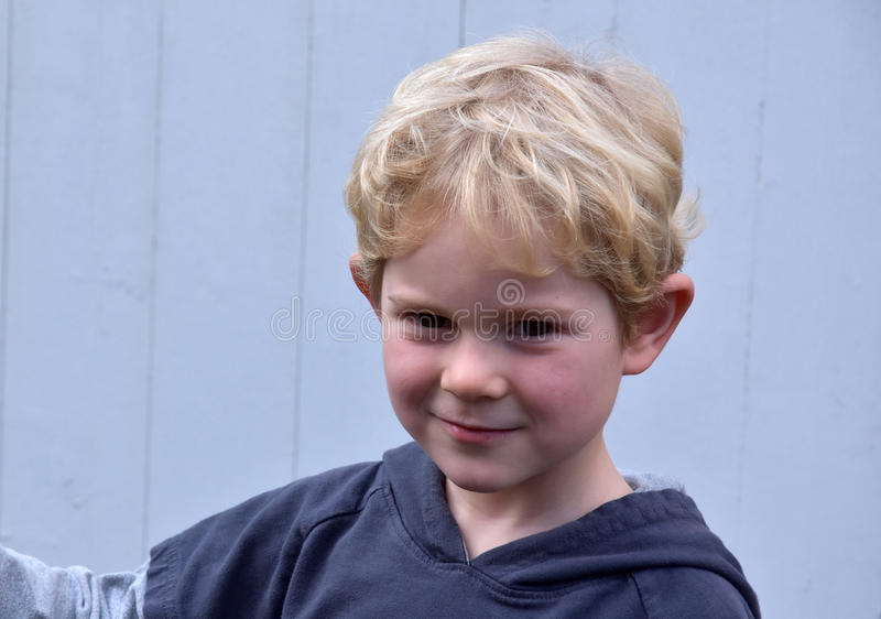 Toddler boy. Portrait of a mischievously toddler boy with blond hair royalty free stock images